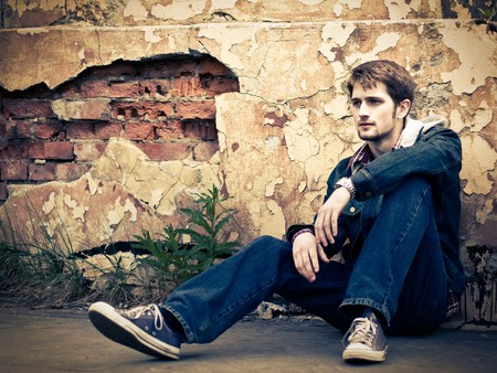 Young man wearing jeans clothes sits on the ground in front of the cracked ruined wall. Stock Photo
