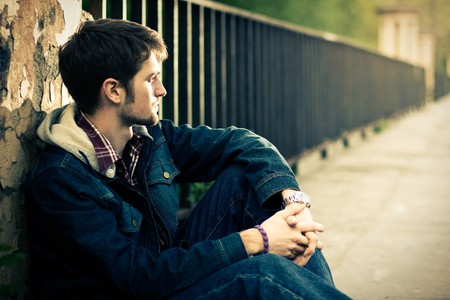 Young man sitting near the fence in sunlight Standard-Bild
