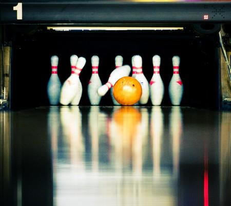 Bowling. Orange ball hits the skittles.