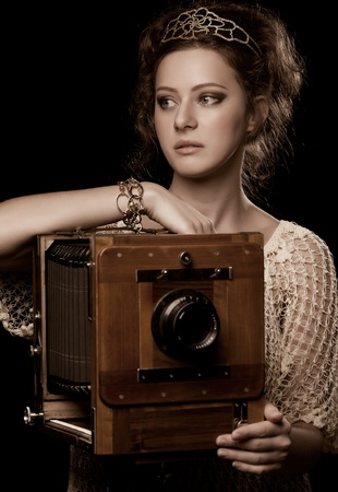 young woman standing near the old-fashioned camera