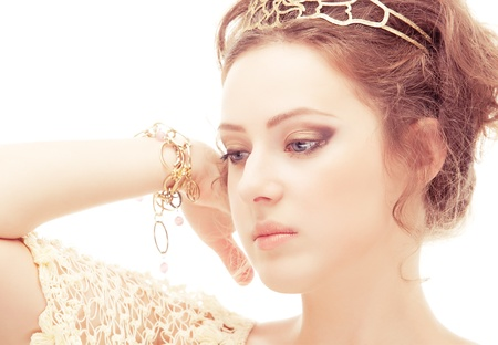 Goddess in a diadem and bracelets of gold, isolated on white background.
