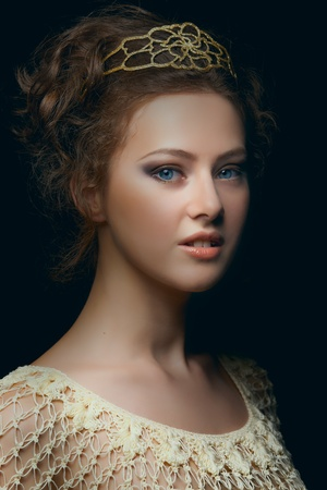 Picturesque portrait of majestic young woman with blue eyes in low key photo