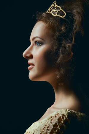 Profile of majestic young woman wearing tiara on black background Stock Photo