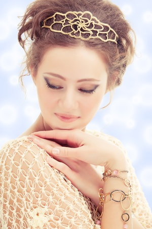 Young shy woman in a diadem and bracelets of gold on abstract background.