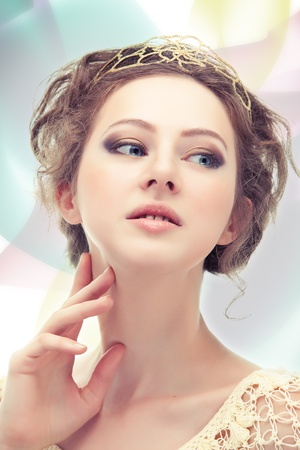 Young majestic woman in a diadem of gold on abstract background. Stock Photo