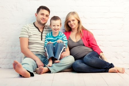 homme enceinte: Famille heureuse de trois assis sur le plancher près du mur mère, le père et le petit garçon mère est enceinte