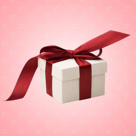 A white box tied with a red ribbon bow on pink abstract background with hearts. The best gift for Christmas, Birthday, Valentiness day or Wedding. photo