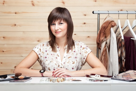 Womans stylist with attributes of her work, standing near coat rack with clothes. Cosmetics and accessories on the table in front of her. photo