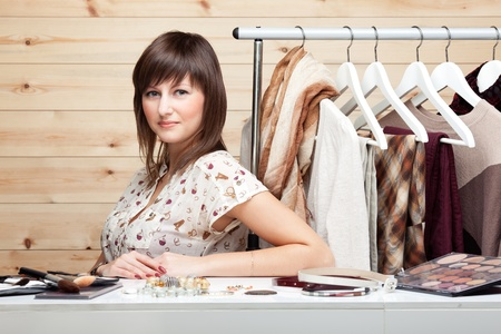 Womans stylist with attributes of her work, standing near coat rack with clothes, cosmetics and accessories on the table. photo