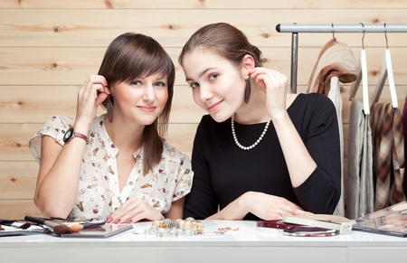 Two young women trying on earrings on wooden background. Clothes, cosmetic and accessories around them