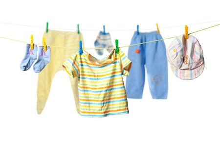 dirty clothes: Baby clothes drying on a rope isolated on white background