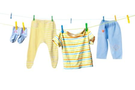 Les vêtements de bébé de séchage sur une corde isolé sur fond blanc Banque d'images