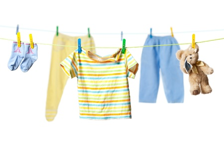 dirty clothes: Baby clothes and a tearful teddy bear drying on a rope isolated on white background Stock Photo