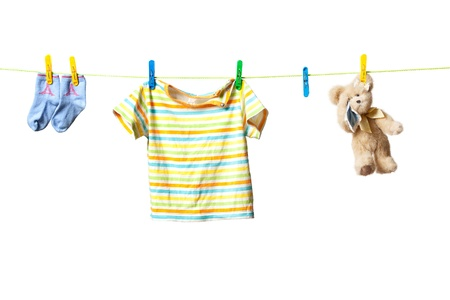 Baby clothes and a teddy bear drying on a rope isolated on white background