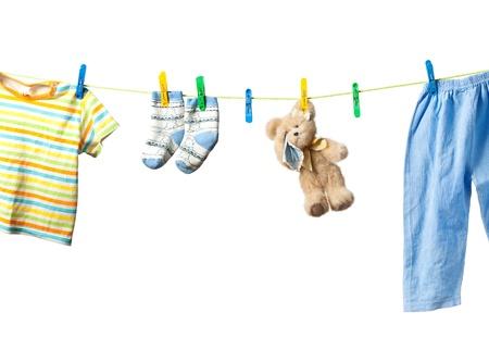 ropa colgada: Ropa de bebé y un osito de peluche de secado sobre una cuerda aisladas sobre fondo blanco