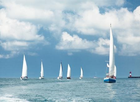 Sailboats sailing, blue cloudy sky and white sails