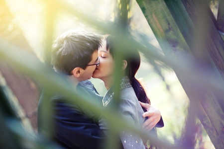 Young couple kissing in the pergola in the autumn park;