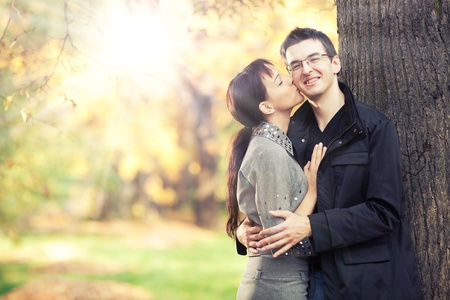 Pretty young girl kisses in cheek her boyfriend in the park; autumn leaves and sunbeams on the background; there is a heart carved on the tree behind Stock Photo - 11784308