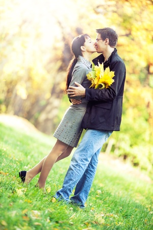 Lovers spend sunny day in the autumn park, they kiss while holding a bouquet of autumn leaves photo