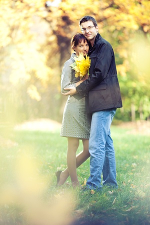 Lovers spend sunny day in the autumn park, they hold a bouqet of autumn leaves; blurs around them photo