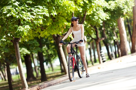 A young woman takes a rest from a bike ride in the park. She