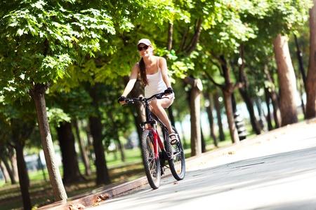 ciclismo: Chica en bicicleta por el parque. Foto de archivo