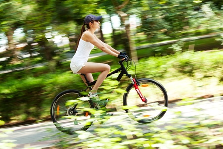Girl cycling in the park. Motion blured image. Standard-Bild