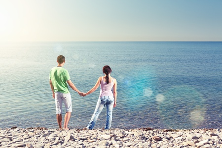 Young couple is standing near water, holding each others arms and looking over the horizon, view from behind, lens flares