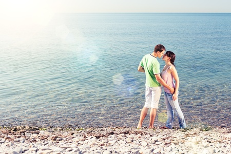 lovers kissing: Young lovers kissing near water, lens flares