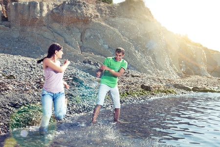 Couple playing in water on the beach, splashes, sunbeams and lens flares, motion blur