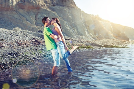 lovers kissing: Lovers kissing passionately while standing ankle-deep in water