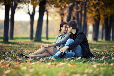 Young couple sitting on the ground in the autumn park Stockfoto