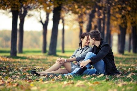 Young couple sitting on the ground in the autumn park Stock Photo - 12859878