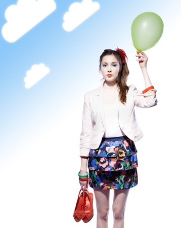 Beautiful girl holding a balloon in one hand and red shoes in another, blue gradient background with clouds