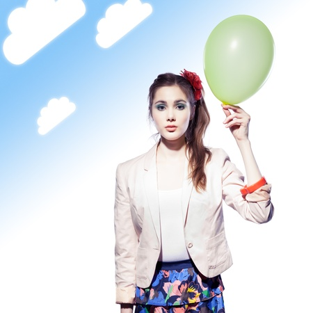 innocense: Beautiful girl holding a balloon, blue gradient background with clouds Stock Photo