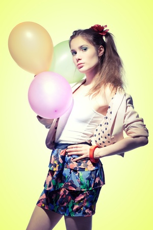 pony tail: Pretty girl with a pony tail holding balloons on yellow background