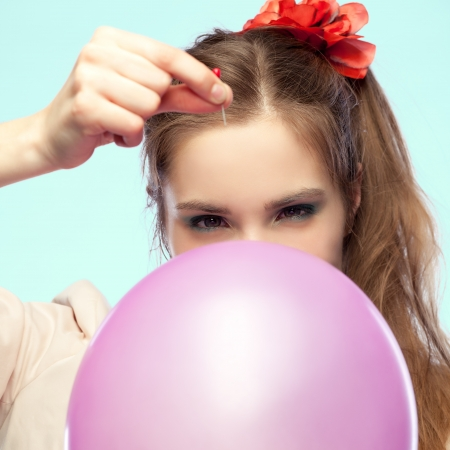 tricky: Pretty girl is going to pop a balloon with a pin