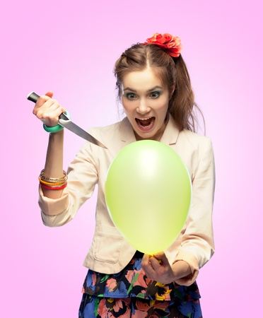 going crazy: Crazy girl is going to pop a balloon with a knife Stock Photo