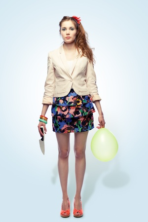 Beautiful sad girl holding a knife in one hand and a balloon in another, blue background photo