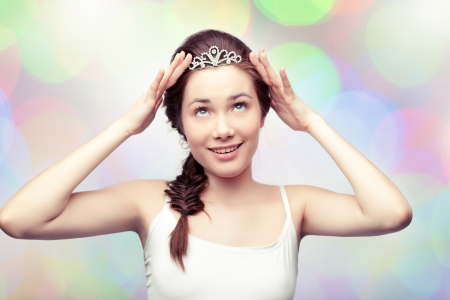 diadem: Beautiful girl is putting on a diamond diadem and admiring it, colorful pastel background Stock Photo