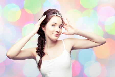 Beautiful girl is putting on a diamond tiara and admiring herself, colorful pastel background Stock Photo