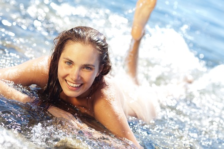 Young tanned woman lying on front and splashing in the surf