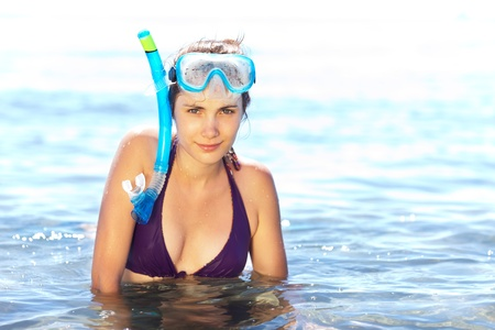 Beautiful tanned girl in snorkel gear chest-deep in water
