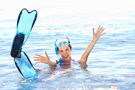 Beautiful tanned girl in snorkel gear in water