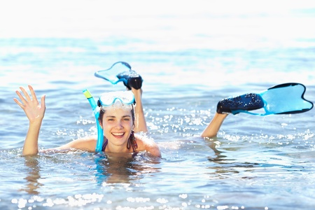 Beautiful tanned girl in snorkel gear waving her hand photo
