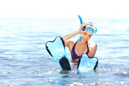 Beautiful tanned girl with snorkeling equipment resting in shallow water