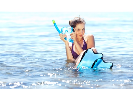 fin: Beautiful tanned girl with snorkeling equipment resting in shallow water