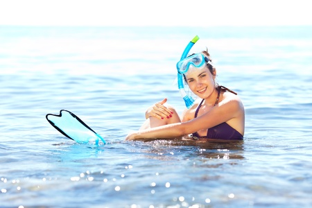 Beautiful tanned girl with snorkeling equipment resting in shallow water photo
