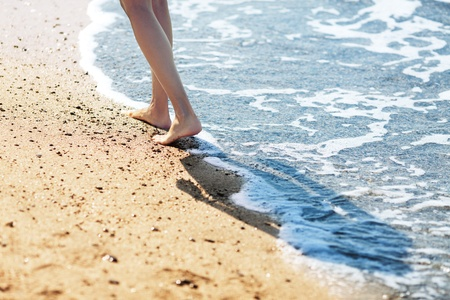 feet in sand: Walking barefoot along the surf on the sand beach