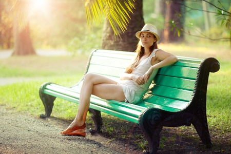 green back: Beautiful girl resting on bench in tropical park